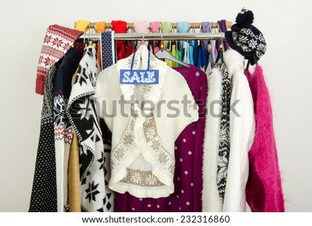 Cute winter sweaters displayed on hangers with a big sale sign. Season clearance rack with colorful winter clothes and accessories. - stock photo