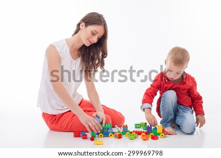 Cute woman and her sun are playing with toys. They are sitting on flooring and smiling. The boy is looking down with concentration. Isolated on background - stock photo