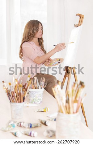 Cute woman artist painting in oils on canvas with brushes in her workshop near window - stock photo