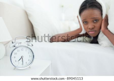 Cute woman being awakened by her alarm clock in her bedroom - stock photo