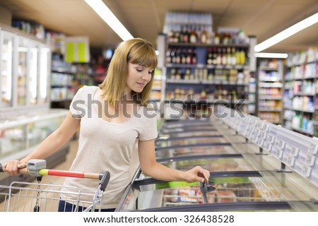 Cute woman chooses frozen products in supermarket - stock photo