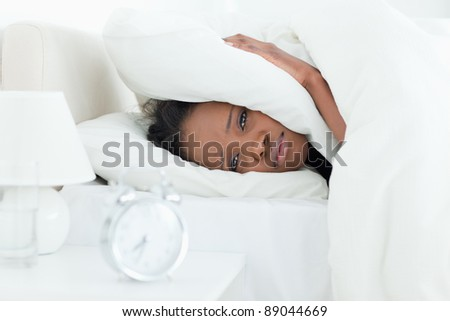 Cute woman covering her ears while her alarm clock is ringing in her bedroom - stock photo