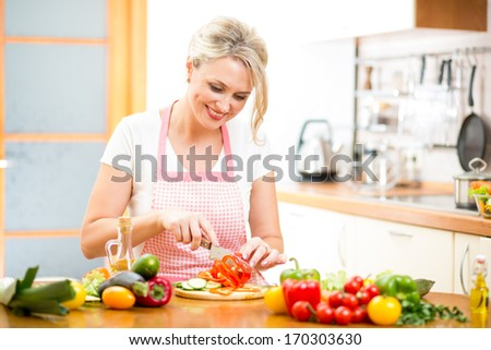 Cute woman cuts paprika for salad sitting at the kitchen table - stock photo