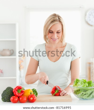 Cute woman cutting vegetables in her kitchen