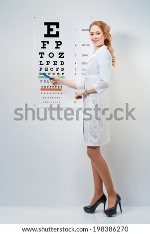 Cute woman doctor - ophthalmologist shows eyesight test chart for eye tests - stock photo