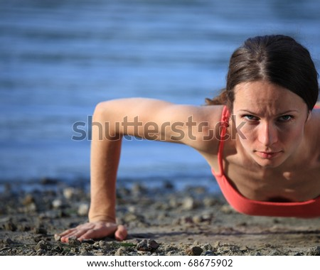 Cute woman doing push-ups on beach. Shot was taken with polarized filter. - stock photo