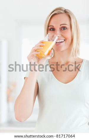 Cute woman drinking orange juice looking into the camera in the kitchen