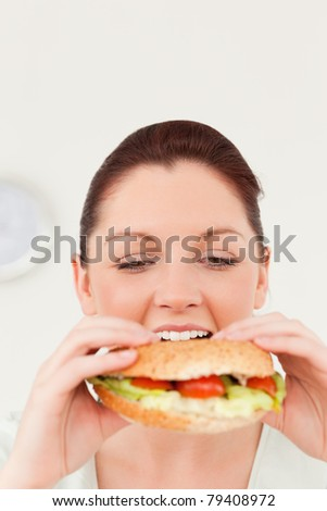 Cute woman eating a sandwich for lunch in her kitchen