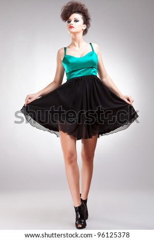 cute woman fashion model taking a bow on gray background - stock photo
