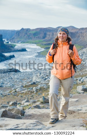 Cute woman hiking in the canyon Dettifoss waterfall in Vatnajokull National Park, Northeast Iceland. Vertical view - stock photo