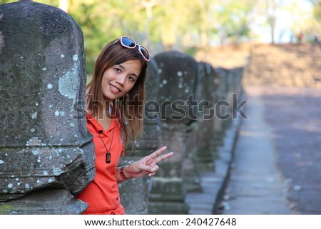 Cute woman in orange clothes up two fingers behind stone post at Phanomrung temple, Thailand