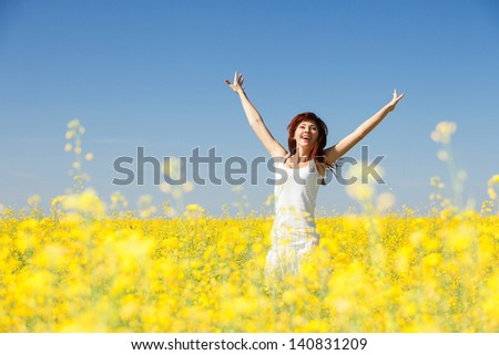 Cute woman in the field with flowers