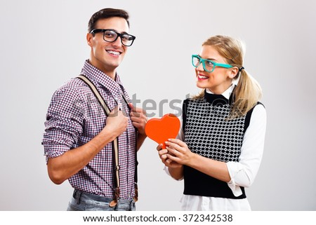 Cute woman is giving heart shape box to her boyfriend.She loves me! - stock photo