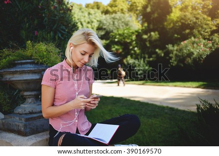 Cute woman is reading pleasant text message on mobile phone while sitting in the park in warm spring day,gorgeous female is listening to music in headphones and searching information on cell telephone - stock photo