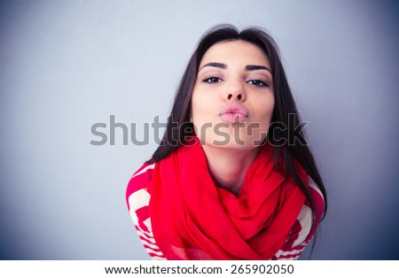 Cute woman kissing at camera over gray background. Wearing in pink scarf and sweater.
