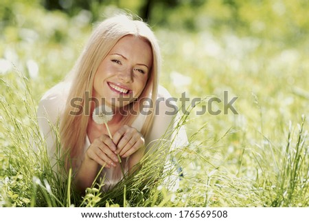 Cute woman lay in the park with dandelions - stock photo
