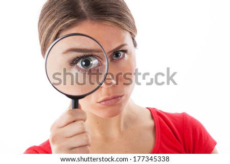 Cute woman looking through a magnifying glass, isolated on white