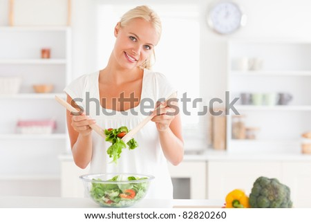Cute woman mixing a salad in her kitchen - stock photo