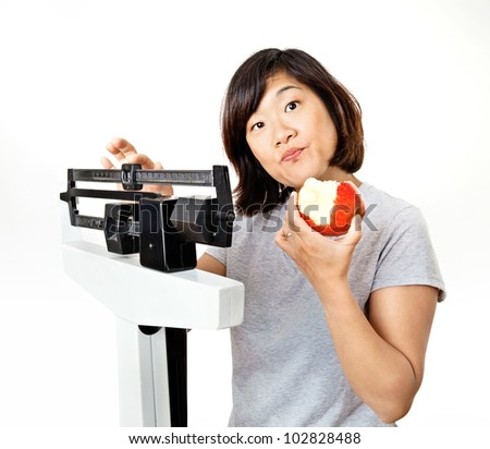 Cute woman on weight scale eating an apple and looking confused. - stock photo