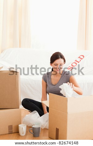Cute woman packing her things in her former home