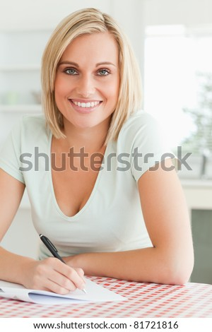 Cute woman proof-reading a text smiles into camera in the kitchen