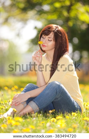 Cute woman rest in the park with dandelions - stock photo
