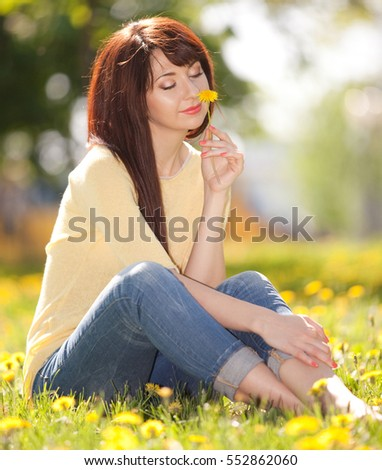 Cute woman rest in the spring park with dandelions. Happy woman relax in flowers at sunny day. Free woman enjoying the nature. Beautiful girl outdoor. Enjoyment and happiness