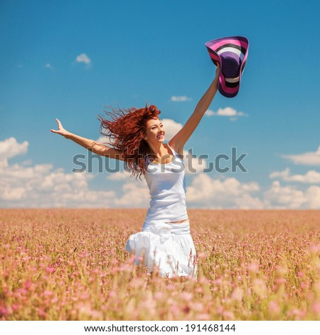 Cute woman running in the field with flowers - stock photo