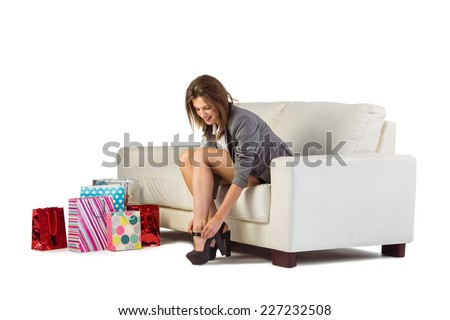 Cute woman sitting on couch taking off her shoes at home in the living room - stock photo