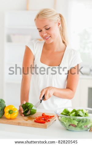 Cute woman slicing pepper in her kitchen