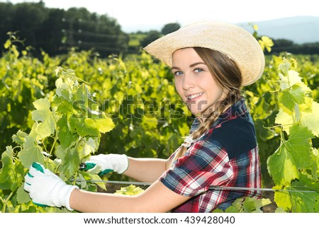 cute woman taking care of plants looking at camera - stock photo