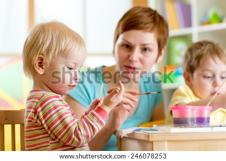 cute woman teaching children to paint at kindergarten or home or playschool