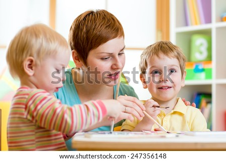 cute woman teaching kids to paint at nursery or playschool - stock photo