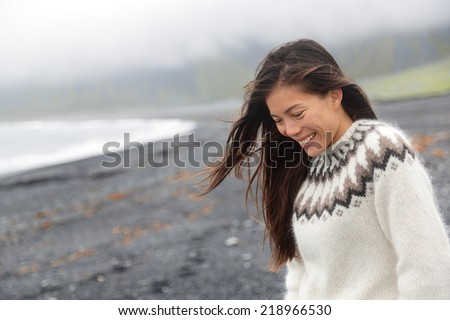 Cute woman walking on black sand beach on Iceland wearing Icelandic sweater. Pretty beautiful adorable multiracial Asian / Caucasian female model looking shy down by the ocean sea smiling happy. - stock photo