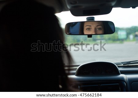 Cute woman with beautiful eyes is looking in rearview mirror in a black car.