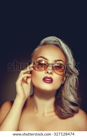 Cute woman with beautiful makeup and stylish sunglasses in studio