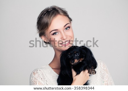 Cute Woman with Dog in Her Hands - stock photo