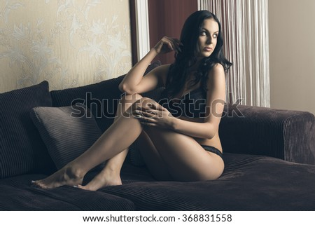 cute woman with long black hair wearing sexy lace lingerie and sitting on velvet sofa in sensual pose  - stock photo
