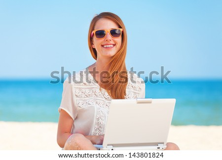 Cute woman with white laptop on the summer beach - stock photo