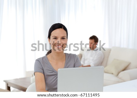 Cute woman working on the laptop while her husband relaxing on the sofa - stock photo