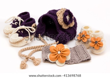 Cute woolen baby hat and booties on white - stock photo
