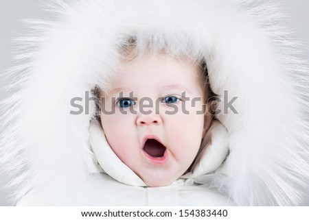 Cute yawning baby girl wearing a huge white fur hat and a warm winter jacket ready for a walk on a cold day - stock photo