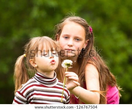 Cute 5 year old and 11 year old (looks into the camera) girls blowing dandelion seeds away. - stock photo