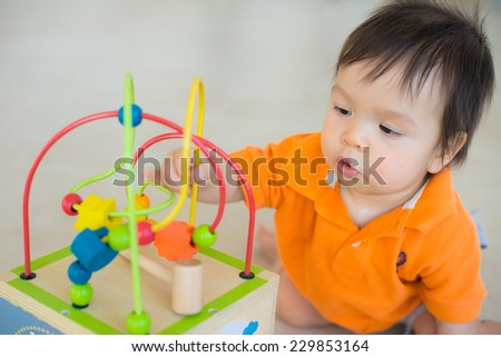 Cute 1 year old Asian Caucasian boy plays with a new toy at home on the floor - stock photo