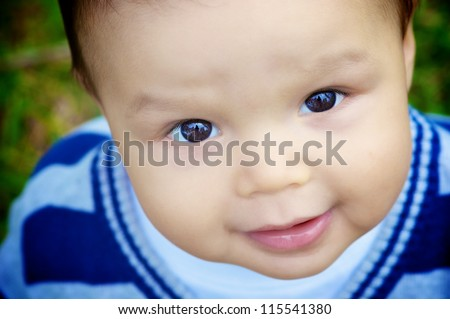 Cute 1 year old Asian Caucasian mixed race boy looks up at camera with big bright brown eyes - stock photo