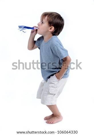 Cute 3 - 4 year old boy blowing his party favor isolated on white