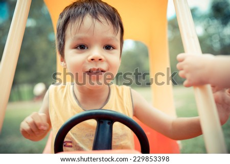 Cute 3 year old mixed race Asian Caucasian boy playing outside in a toy car - stock photo