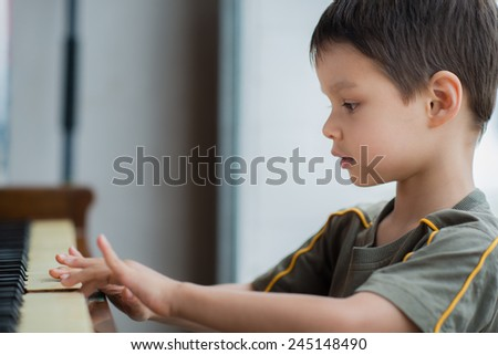 Cute 4 year old mixed race Asian Caucasian boy plays an old piano - stock photo