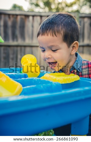 Cute 2 year old mixed race Asian Caucasian boy plays happily with a water toy in his suburban house backyard. Filtered effects - stock photo