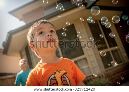 Cute 2 year old mixed race Asian Caucasian boy plays happily with bubbles in his family home backyard - stock photo
